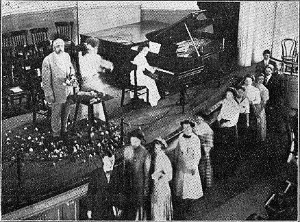 "Millikin students ""shower"" Taylor with flowers on the stage, October 19,1911 Decaturian"