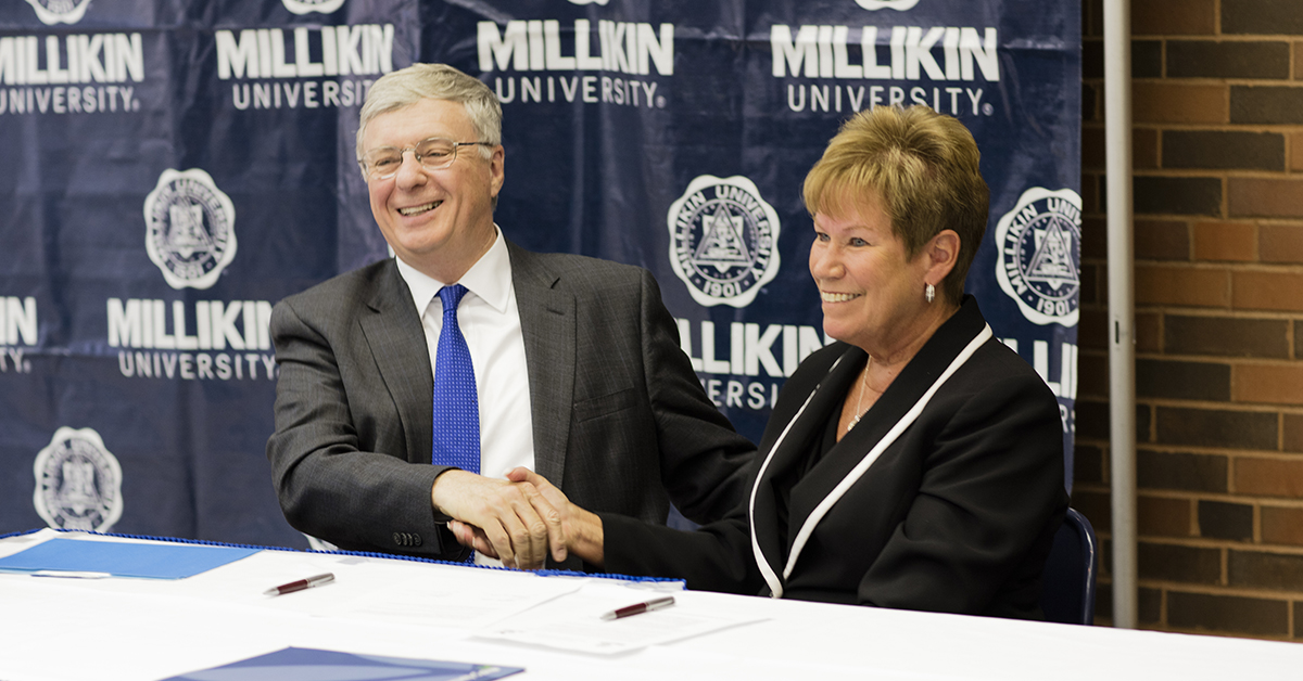 Millikin president Patrick White and Richland president Gayle Saunders shake hands after signing agreement