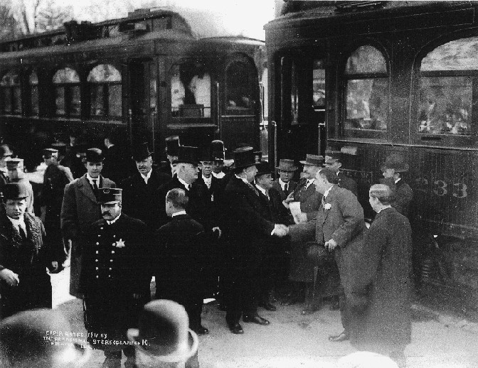 Image of President Taft shaking hands as he prepares to board the ITS train to Springfield on West Main St. in front of Millikin