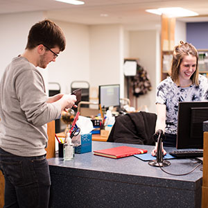student at library help desk