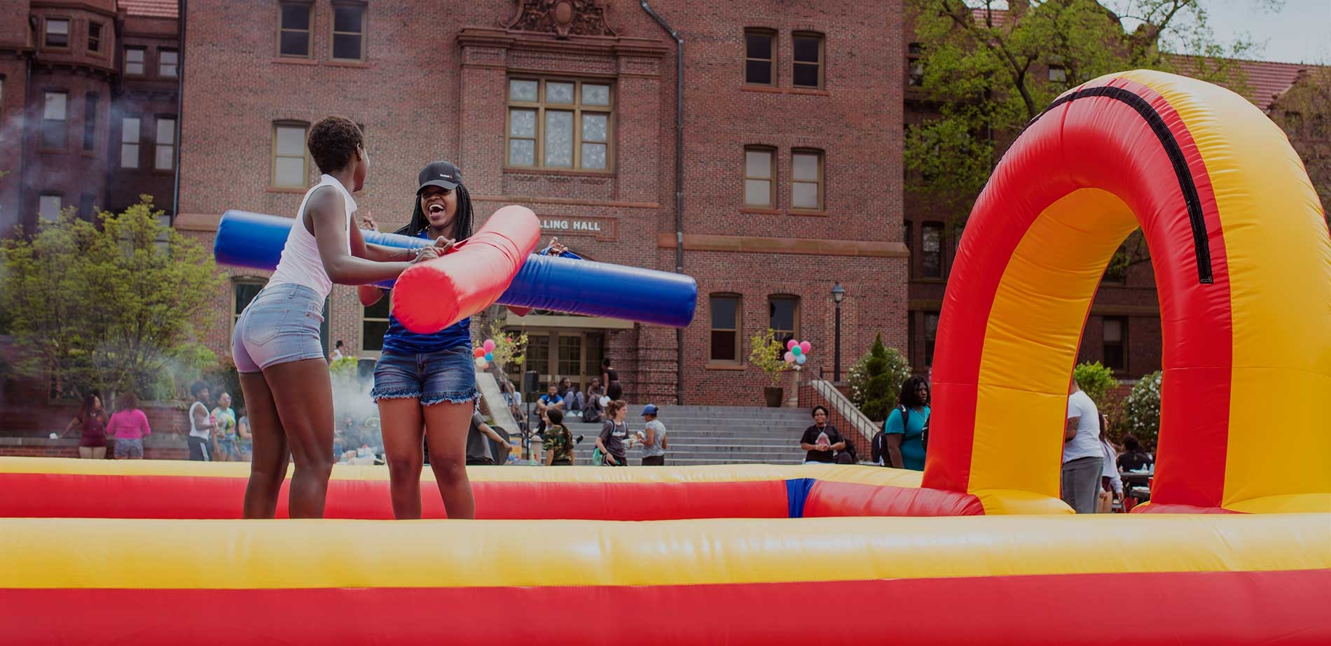 students battling in inflatable on the quad