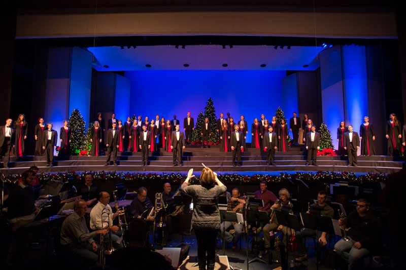 large stage with choir singers and orchestra pit surrounded by Christmas decor